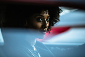 woman sitting in a car gazing outside of window