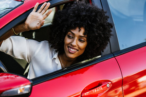 woman waves out of open window of car