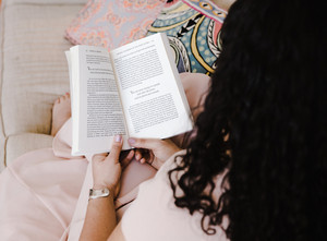 woman with an open book reads on the couch