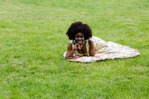 Woman with big afro lays in the grass