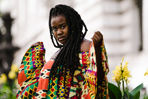 woman with braids has a colorful dress on