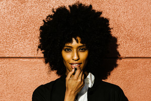 woman with curly afro standing against wall applying lipstick