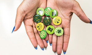 woman with green nails holds up St. Patricks Day buttons in her hands