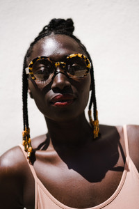 woman with large sunglasses and braids wearing red lipstick