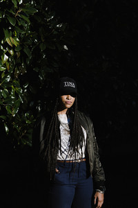 woman with long braids  in a hat and leggings in the nighttime