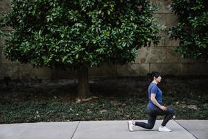 Women does plank exercises on sidewalk