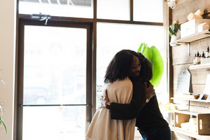 women hugging one another in the entrance of a wellness store