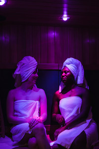 women sitting in a sauna with spa towels on their heads
