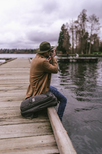 young asian man sits and takes pictures of lake