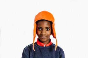 young Black boy in a bright orange winter hat
