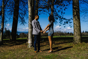 young Black couple pose for engagement pictures in a scenic background surrounded by trees