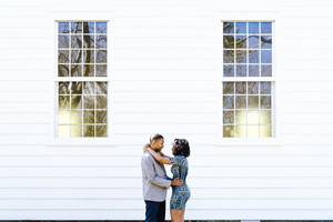 young Black couple pose for engagement pictures in front of a brick building