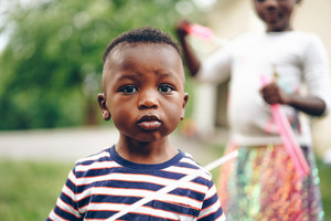 Young, black Ghanaian boy playing with toy