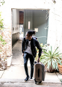 young black man rolls suitcase next to him