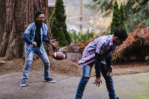 young boys play with a football outside