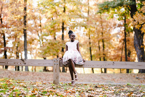 Young child in a dress sits on a fence surrounded by autumn leaves