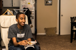 young man in college eating pizza in his dorm room