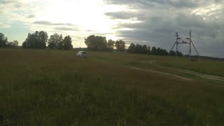 Aerial - car driving throught the field, in the evening, country road, bad road, byroad