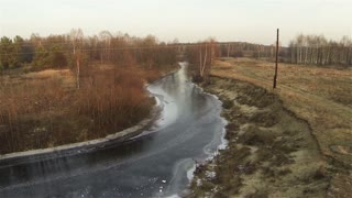 Aerial down flight to autumn icy river