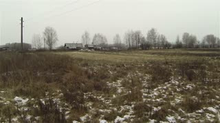 Aerial view of  abandoned house old farm at country side, first snow, plowed field, dog greyness