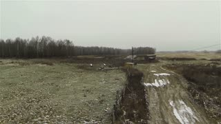 Aerial view of dirty road at farm in country side, russia first snow, autumn, bad weather
