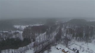 Aerial view of russian frozen forest in winter near village in country side, snowy weather, snowstorm