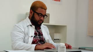 African american male doctor working on laptop at his desk