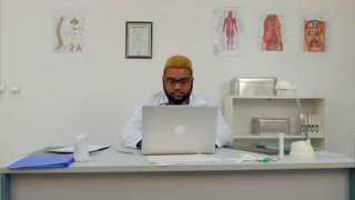 African american male doctor working on laptop