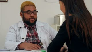 Afroamerican doctor prescribing pills to female patient and explaining dosage