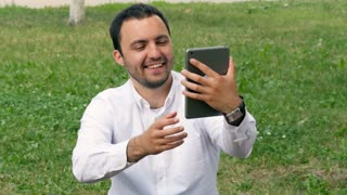 Amazing man taking selfie with digital tablet in the park