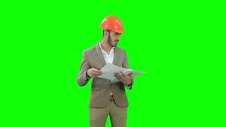 Architect in helmet checking construction plan on a Green Screen, Chroma Key