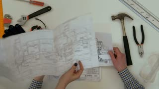 Architect working on blueprints when female colleague bringing more drawings