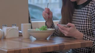 Arms of young businesswoman using a smartphone for communication. She is sitting at the table in cafe and eating a salad