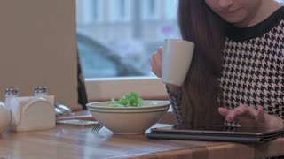 Arms of young businesswoman using a tablet for communication. She is sitting at the table in cafe and eating a salad