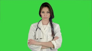 Attractive young female doctor in white coat with stethoscope looking into the camera on a Green Screen, Chroma Key