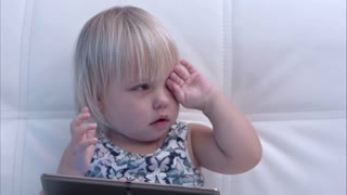 Baby girl with tablet rubbing her eyes after crying