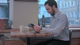 Bearded businessman using tablet computer in coffee shop