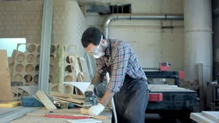 Bearded carpenter in safety glasses working with electric planer in workshop