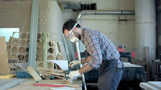 Bearded carpenter working with electric planer on wooden plank in workshop