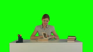 Beautiful female student read book on a Green Screen