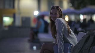 Beautiful girl sitting on a bench at embankment in the evening smiling and looking in a distance