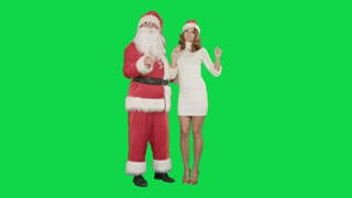 Beautiful happy woman dancing with Santa Claus on a Green Screen Chrome Key
