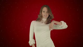 Beautiful woman dances on red background with snow