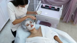 Beautiful woman getting facial mask at beauty salon
