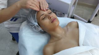 Beautiful young woman getting facial massage with closed eyes in a spa salon