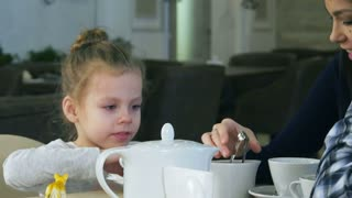 Blond cute girl tries to put sugar in her cup of tea. Her mother helps her