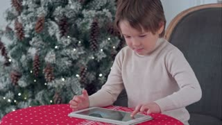 Boy playing games on his tablet sitting at the table near the Christmas tree