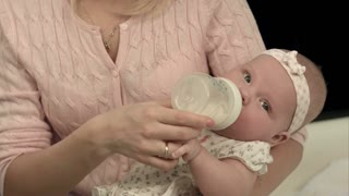 Bright mother feeding milk from bottle her adorable son at home