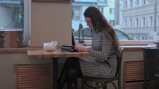 Business woman use Tablet in the morning at restaurant while waiter service her