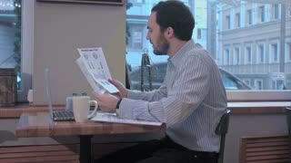 Businessman in a cafe reading with interest a contract document